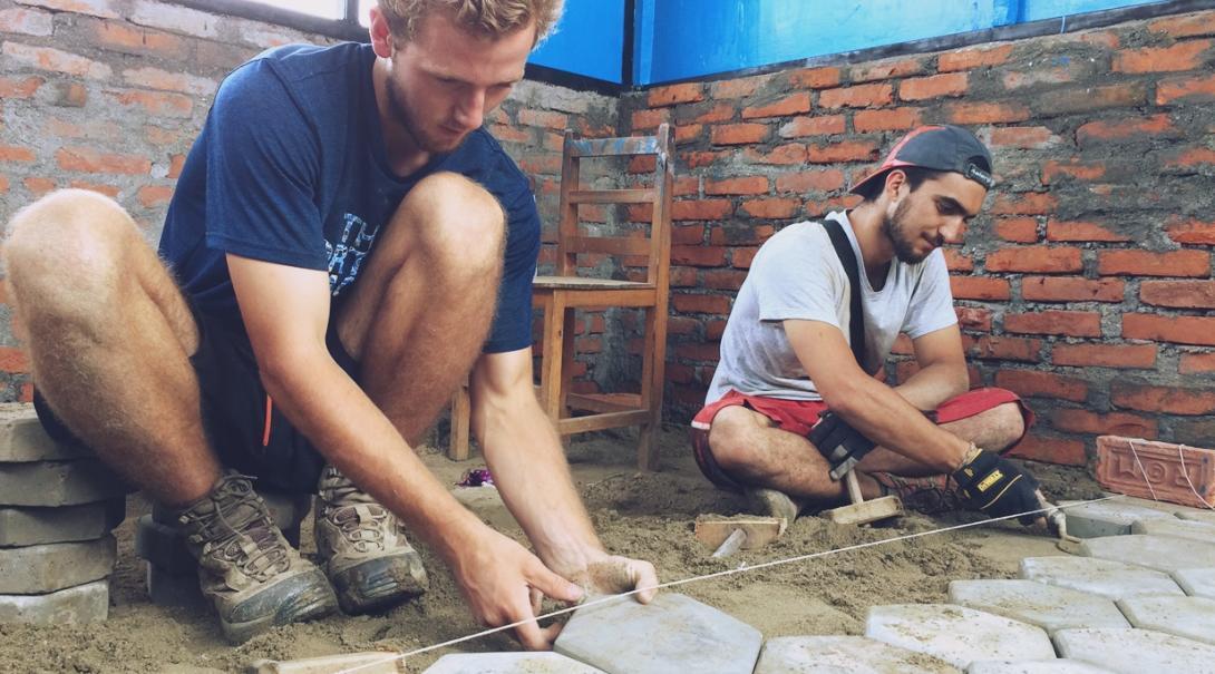 ネパールの学校の床の設置に励む建築ボランティア